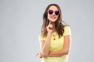 summer, valentine's day and people concept - smiling young woman or teenage girl in yellow t-shirt and heart-shaped sunglasses over grey background