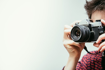Young man is taking a picture with a vintage camera