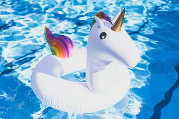 Inflatable colorful white unicorn at the swimming pool. Vacation time in the swim pool with plastic toys. Relaxation and fun concept. Ripple Water in swimming pool with sun reflection