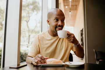 New day welcome.Young confident African man enjoying his morning coffee and french croissant while sitting at modern urban cafe