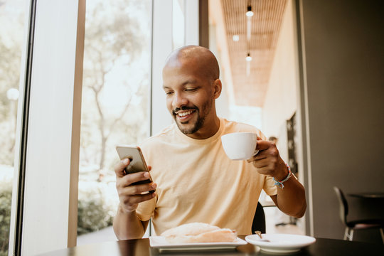 Happy cheerful African hipster holding mug, drinking fresh cappuccino, browsing internet and checking newsfeed on social media.Man using cell phone during coffee break at modern cafe