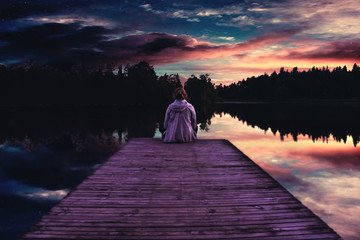 picture of a girl sitting at a lake in the sunset on a warm evening with the cloudy sky reflecting in the water