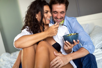 Happy young couple eat breakfast in bed in morning