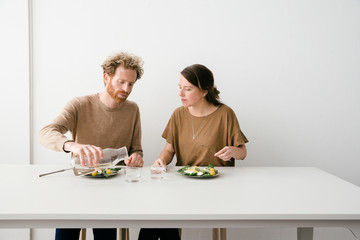 Thirty something European couple sitting down for a avocado salad lunch together looking at each other.