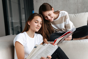 Two cheerful teenager girls friends sitting at home