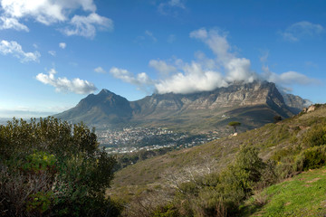 Clouds spilling over Table Mountain on a clear day, Cape Town, South Africa