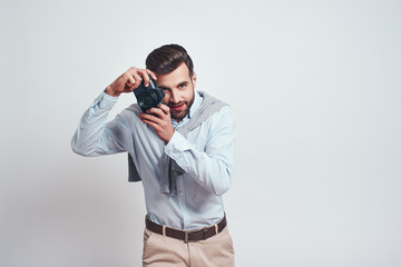 Nice shot. Attractive young man in casual wear is photographing you while standing in studio on a grey background