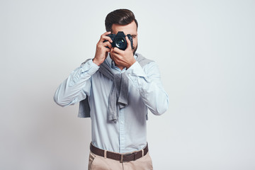 Do what you love. Young bearded man in blue shirt taking picture with camera isolated on grey background.