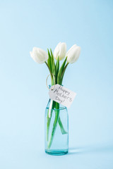 bouquet of white tulips in glass vase with happy mothers day greeting label on blue background