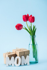 gift boxes, bouquet of red tulips and white paper word mom on blue background