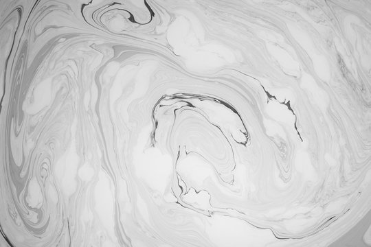 Abstract monochrome marble background. Stains of paint on the surface of the water.