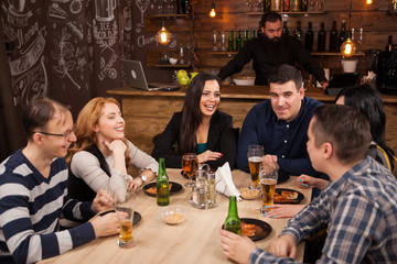 Group of young friends sitting around table in bar togethe