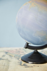 Selective focus of spinning globe and map isolated on blue