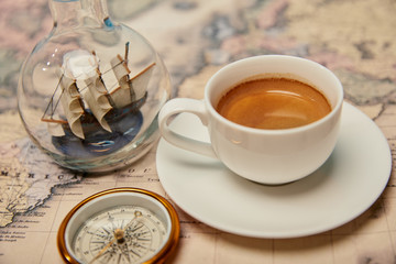 coffee cup, compass and toy ship in glass bottle on world map