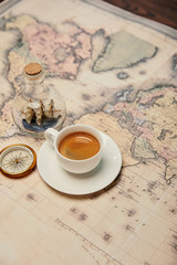 coffee cup and saucer, compass and toy ship in glass bottle on map