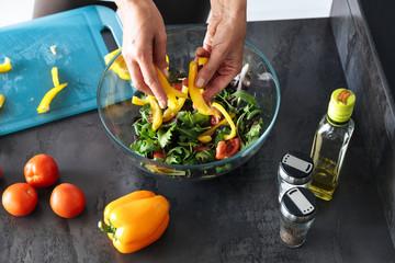 Attractive healthy woman cooking salad