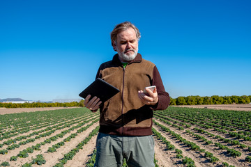 A farmer uses his tablet and his mobile in his field.