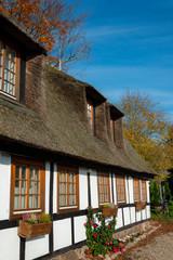 Reetdachhaus mit Fachwerk und Sprossenfenstern