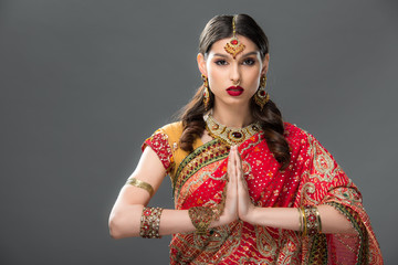 indian woman in traditional clothing and accessories with namaste mudra, isolated on grey
