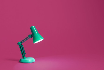Retro green desk lamp turned on and bent over shining on a bright pink background.  Landscape orientation with a left side composition leaving room for text and copy space. Wall mural
