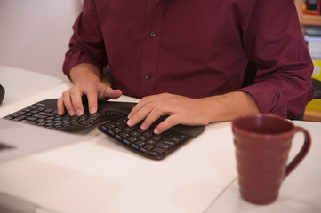 Male professional using an ergonomic keyboard, sitting at a desk. Cropped shot of a man typing, in an office or a work designated environment, with cup of coffee in burgundy color matching the shirt