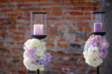 Minimalist outdoors two candle holders with pastel colored hydrangeas bouquets at the basis, decorative element for a formal event or a wedding, with a terracotta color brick wall in the background