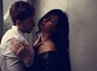 Sexy couple portrait. Man in white shirt kissing his sensual beautiful girlfriend in neck