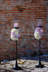 Two outdoors free-standing candle holders with pastel colored hydrangeas bouquets at the basis, decorative element for a formal event or a wedding, with a terracotta color brick wall in the background