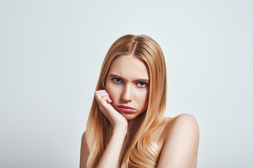 Bored. Upset young blonde woman looking at camera and making a sad face while standing in studio on a grey background