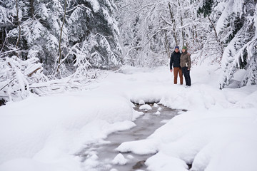 Fototapete - Smiling couple standing by a frozen river while out hiking