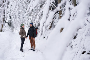 Fototapete - Young couple holding hands while out for a winter hike