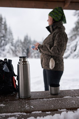 Fototapete - Young woman warming up with coffee during a winter hike