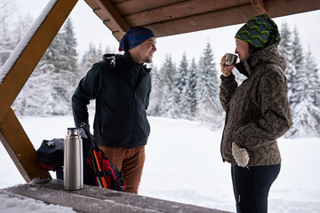 Fototapete - Smiling couple warming up with coffee during a winter hike