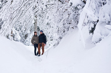 Fototapete - Smiling couple standing on a snow covered path while hiking