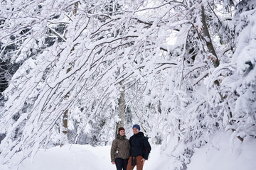 Fototapete - Smiling couple standing in a snow covered forest while hiking