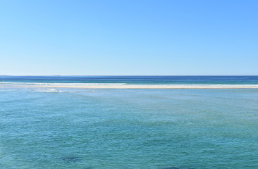 Beach background with sand, turquoise water and horizon over sea. Blue sky, sunny day. Galicia, Rias Altas, Spain.