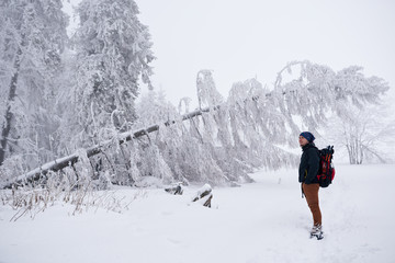 Fototapete - Young man appreciating a snow covered winter landscape