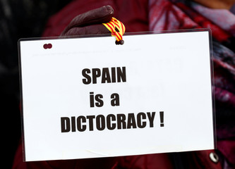 A pro-independence Catalan holds a sign during a protest in front of the EU Commission headquarters in Brussels