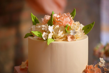 Elegant formal tiered cake with top beautifully decorated with icing sugar flowers and covered in velvety royal icing prepared for a wedding, banquet, birthday or garden party or a formal event