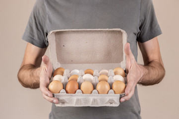 Caucasian man with gray tshirt holding a cardboard egg box full of chicken eggs