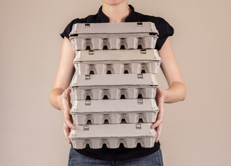 Caucasian woman with black shirt holding four cardboard egg boxes full of chicken eggs