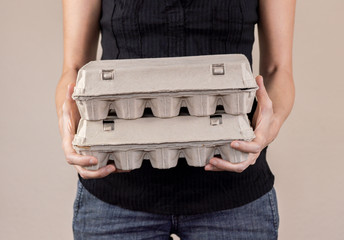 Caucasian woman with black shirt holding two cardboard egg boxes full of chicken eggs