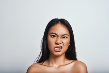 Disgust. Displeased asian woman with long hair making a face and feeling unhappy. Negative emotions