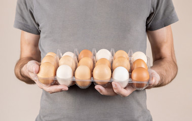 Caucasian man with gray tshirt holding a plastic egg box full of chicken eggs