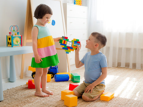 A boy and a girl are holding a heart made of plastic blocks. Brother and sister have fun playing together in the room.