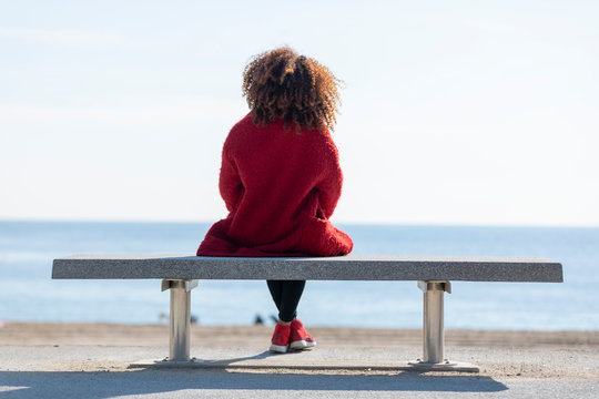 Rear view of a young curly woman wearing red denim jacket sitting on a bench while looking away to horizon over sea