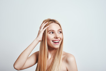 Feeling free and happy. Attractive young woman with naked shoulders touching her hair, looking away and smiling in studio on a grey background