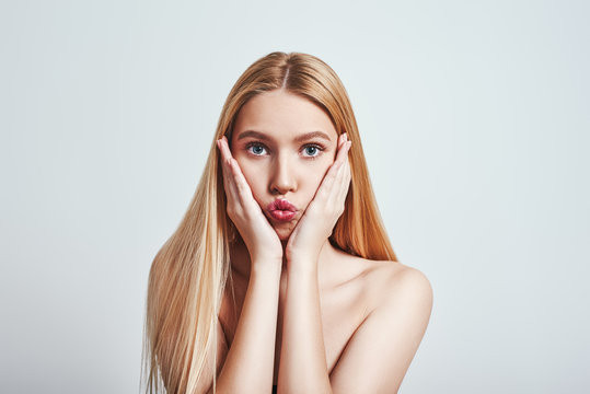 What should i do? Young woman with long blond hair looking at camera and making a face while standing against grey background