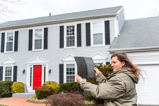 Young unhappy woman female homeowner standing in front of house on windy day in coat jacket during winter storm holding roof tile shingle inspecting damage