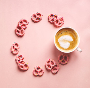 Cup of coffee with art heart shape and Strawberry flavoured yogurt covered pretzels on pink background. Love concept. Flat lay, top view